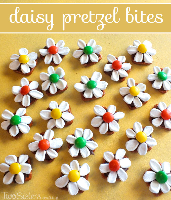 Daisy Pretzel Bites made with pretzels, Hershey Kisses, Marshmallows and M&M's. This delicious treat looks like a daisy but tastes like a s'more! Pin this fun spring and summer dessert for later and follow us for more fun and tasty pretzel bite ideas.