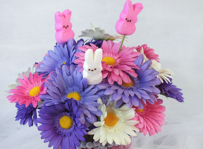 This adorable Easter Centerpiece will be everyone's favorite Easter decoration - so fun and so easy to make. All you need are M&M's, Peeps and some flowers to make this cute DIY Easter Craft. Follow us for more fun Easter ideas.