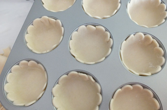 Press pie dough into the muffin tins