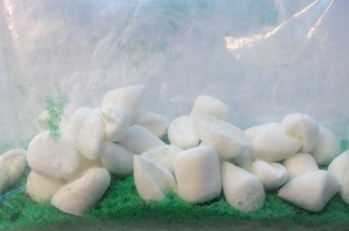 Dump marshmallow pieces into the colored sugar