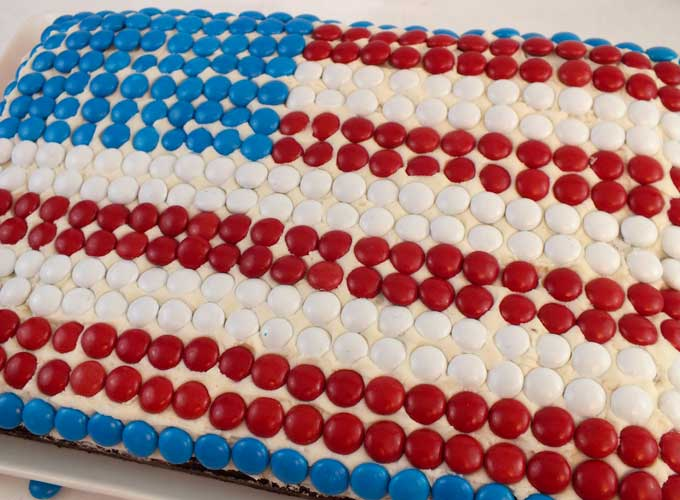 This M&M Flag Cake could not be easier to decorate and it is a great last minute Fourth of July dessert for a 4th of July party, a Memorial Day BBQ or an Olympics viewing party. Pin this great 4th of July treat for later and follow us for more fun and patriotic 4th of July Food Ideas.