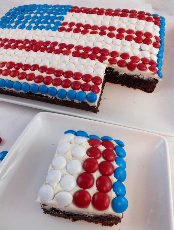 This M&M Flag Cake could not be easier to decorate and it is a great last minute dessert for a 4th of July party or a Memorial Day BBQ. Follow us for more fun and patriotic 4th of July Food Ideas.
