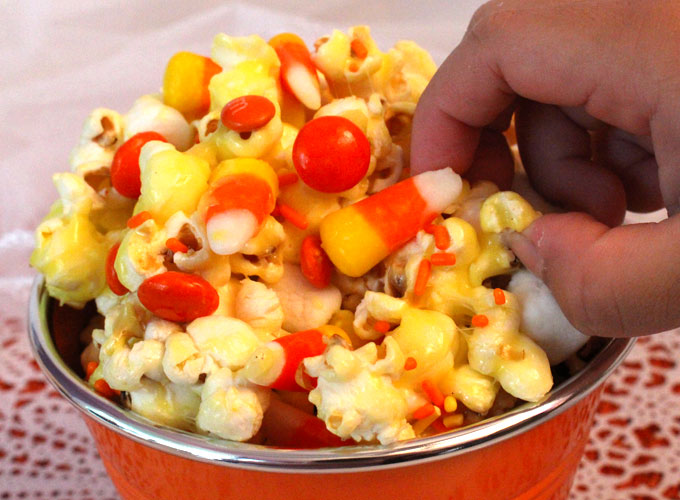 Candy Corn Popcorn - a fun Halloween treat. Sweet, salty, crunchy and delicious and it is so easy to make. It would be a great Halloween Party Food or a movie night dessert! Follow us for more fun Halloween Food ideas.