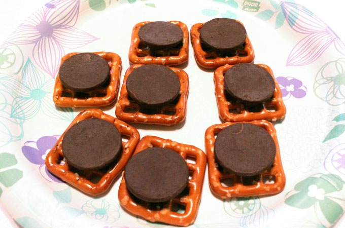 Melting the chocolate wafers on the pretzel snaps