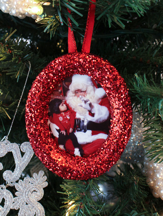 These DIY Glitter Photo Christmas Tree Ornaments are beautiful and easy to make. These handmade sparkling picture frame ornaments will display your favorite family holiday memories right there on your Christmas Tree for all the years to come. Pin this fun Christmas Craft for later and follow us for more great Christmas Decoration ideas and crafts.