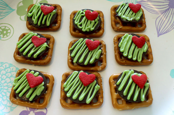 Adding the red heart to the Grinch Pretzel Bites