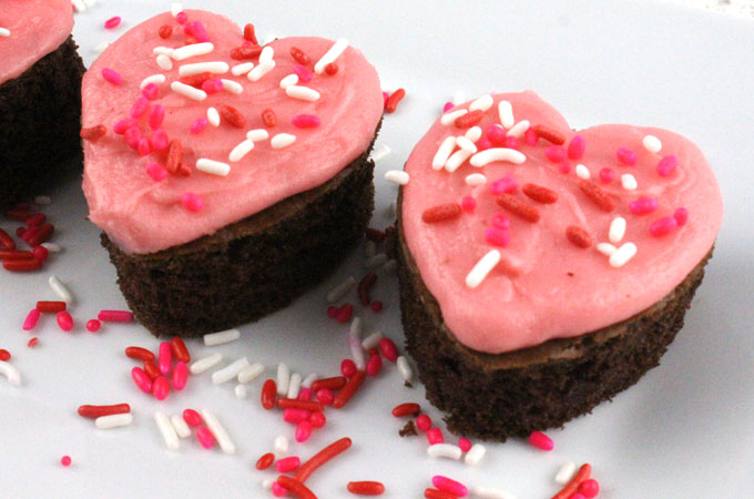 Valentines Cake Bites - fun and delicious mini cakes with pretty pink Buttercream frosting. A great Valentines Day dessert idea and a unique take on a Valentines cupcake. Super easy to make, they will be a great Valentine's Day treat for this year's party. Follow us for more Valentine's Day Food ideas.