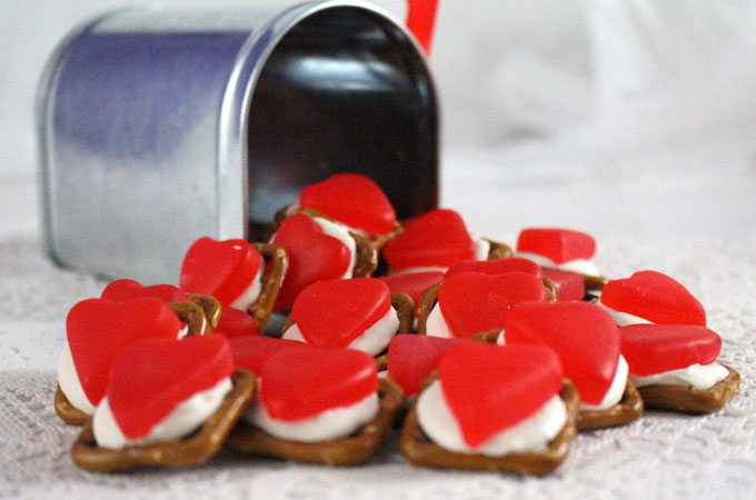 Gummy Hearts Pretzel Bites - Yummy bites of sweet and salty goodness. Our easy to make treats are the perfect Valentine's Day Treat. Iconic Juju Cherry Hearts candy combine with crunchy pretzels for a unique Valentines dessert. Pin this great Valentine's Day dessert for later and follow us for more fun Valentines Food Ideas.