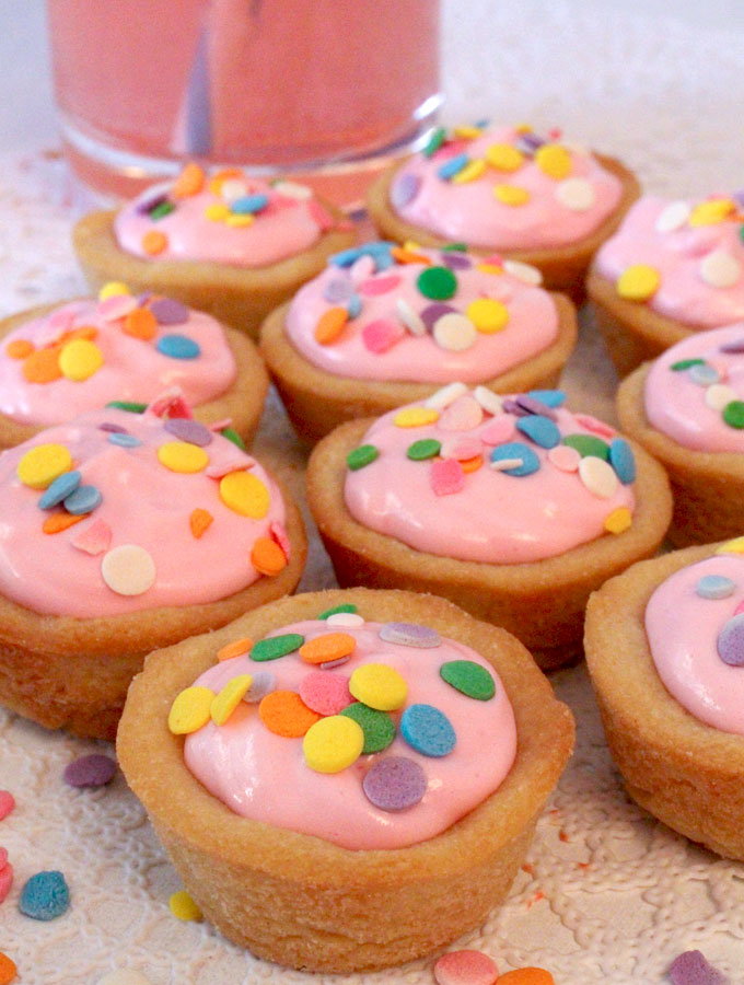 Pink Lemonade Cookie Cups - the perfect blend of sweet and tart. These yummy cookie bites are easy to make and look so pretty. They would be a great Easter dessert, Mother's Day Brunch Treat or summer cookie. Follow us for more great Easter Food ideas.