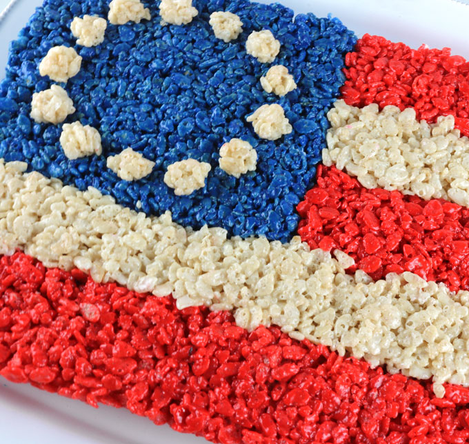 Wow your family and party guests with our American Flag Rice Krispie Treat - a patriotic dessert that is both delicious and easy to make. It would be a great 4th of July dessert, a Memorial Day BBQ treat or even an Olympics viewing party snack. Pin this delicious Fourth of July treat for later and follow us for more great 4th of July Food Ideas.