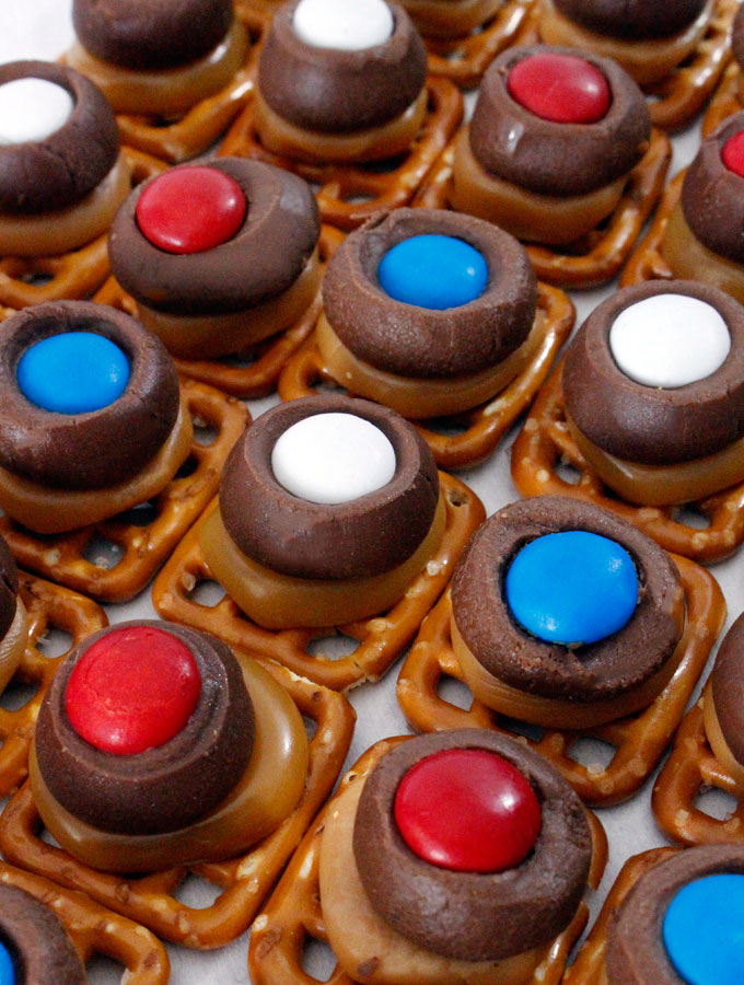 These Patriotic Caramel Pretzel Bites are great 4th of July treats. Sweet, salty, crunchy and delicious they are great Red White and Blue dessert for 4th of July, Memorial Day or even an Olympics viewing party. Pin this fun Fourth of July dessert for later and follow us for more 4th of July Food ideas.