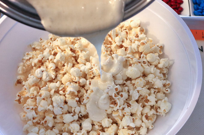 Pour marshmallow mixture into the bowl of popcorn