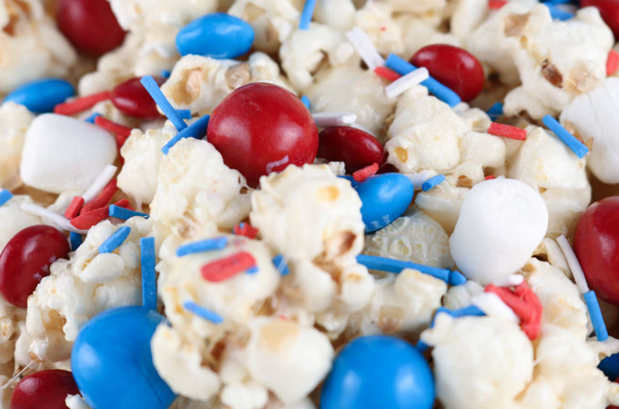 Celebrate with our Patriotic Popcorn - a fun 4th of July Dessert that is both sweet and salty and chock full of Red White and Blue Candy. This yummy Fourth of July treat is super delicious and so easy to make. It would be great at a 4th of July Party, a Memorial Day barbecue or an Olympics viewing party. Pin this yummy 4th of July popcorn recipe for later and follow us for more great 4th of July Food Ideas.