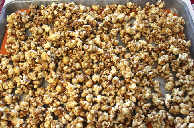 Pour caramel corn onto a cookie sheet