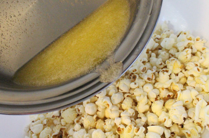 Pour butter onto popcorn