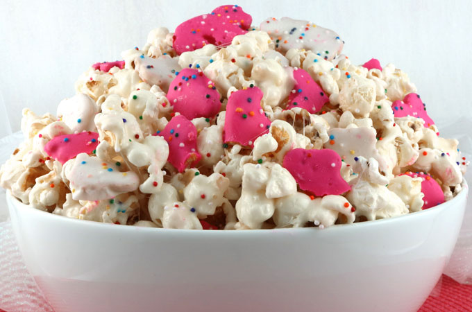 Circus Animal Popcorn - sweet and salty popcorn, covered with marshmallows and yummy Circus Animal Cookies just for fun! A great popcorn treat that is so easy to make! A delicious snack and so very pretty with the sprinkles and the pink and white cookies. Pin this easy dessert for later and follow us for more great Popcorn Recipe Ideas.