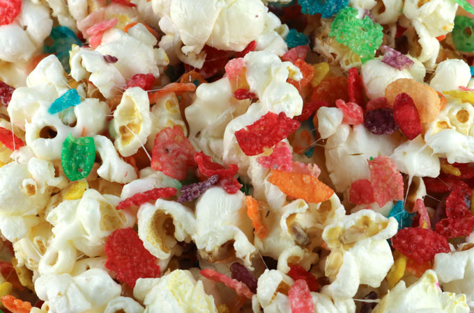 Yabba Dabba Doo! It's our Fruity Pebbles Popcorn - sweet, salty, fruity and delicious and so easy to make. We've mixed a grown up snack with a beloved childhood cereal and boy does it make for a delicious dessert. The colors from the Fruity Pebbles are so pretty that it would also make a beautiful Fall Dessert idea. Pin this fun popcorn treat for later and follow us for more great Popcorn Recipe Ideas.