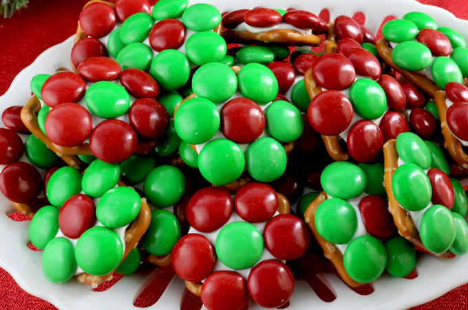 Christmas Flower Pretzel Bites - yummy bites of sweet and salty goodness that are perfect for this year's Holiday Party. Your party guests will love these unique and delicious Christmas Treats (and you don't have to tell them how easy they are to make!) Pin this festive Christmas Dessert for later and follow us for more fun Christmas Food Ideas.