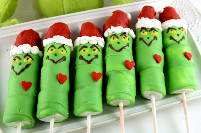 Grinch Marshmallow Pops - a fun Christmas Treat. These The Grinch shaped candy coated marshmallows on a stick are so adorable and so fun to make. They would be perfect for a Holiday Bake Sale or a How the Grinch Stole Christmas family movie night. Pin this adorable Christmas Dessert for later and follow us for more great Christmas Food Ideas.