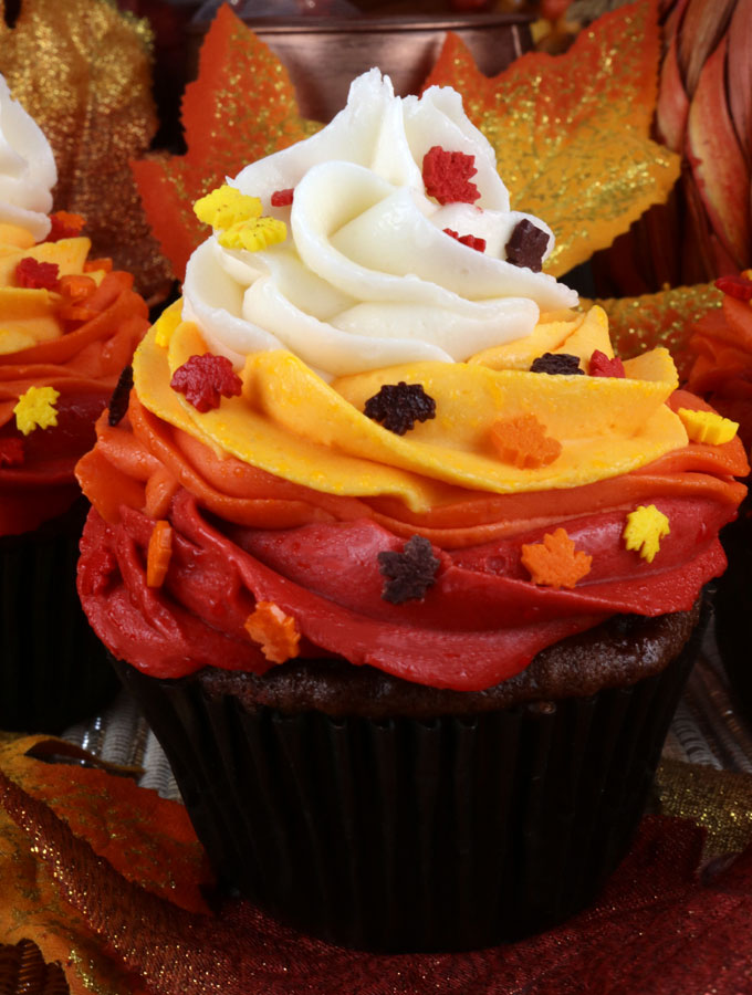 Harvest Swirl Cupcakes - gorgeous and delicious and perfect for Fall and nobody needs to know how easy these Thanksgiving Treats are to make. Topped with beautiful Buttercream Frosting in Fall colors these Fall Cupcakes would be perfect for a Fall Bake Sale or as a Thanksgiving dessert for your guests who don't like pie. Pin this yummy Thanksgiving Dessert for later and follow us for more great Thanksgiving Food Ideas.
