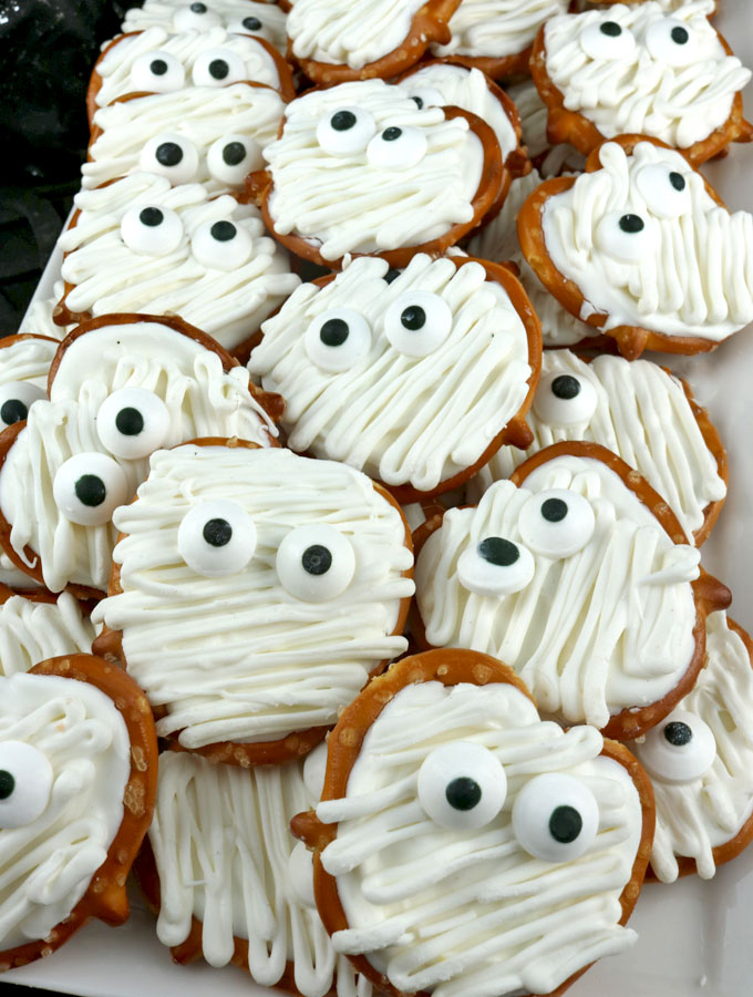 Mummy Pretzel Bites - you'll only need pretzels and candy melts to make these adorable sweet and salty Mummy Halloween treats. We have step by step instructions on how to make this fun Halloween Dessert for this year's Halloween Party. Pin this easy Halloween Candy for later and follow us for more great Halloween Food Ideas.