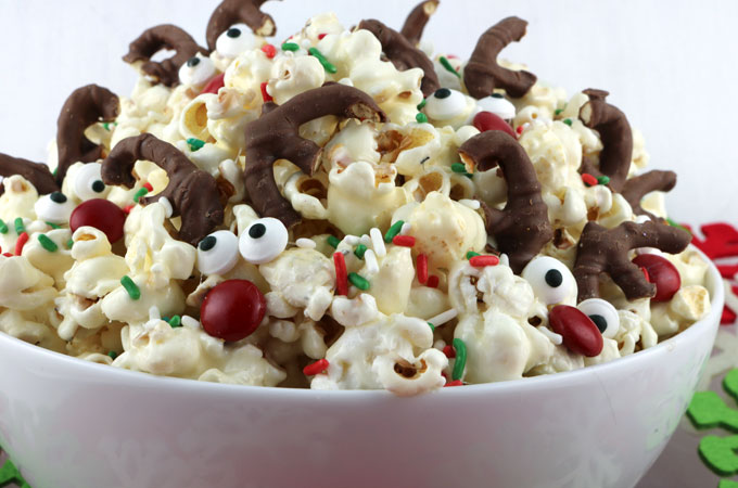 Reindeer Popcorn - sweet, salty, delicious and look at those adorable candy Reindeer! Yum, yum, yum. This fun popcorn recipe would be a great Christmas Dessert for a Holiday Party or a Christmas Family Movie Night. Pin this easy to make snack Christmas Treat for later and follow us for more fun Christmas Food Ideas.