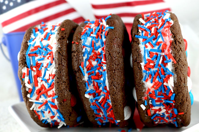 Patriotic Ice Cream Sandwiches - chocolate cookies with Red White & Blue M&M's and creamy vanilla ice cream make for a delicious 4th of July dessert. They are perfect as a extra treat at a Fourth of July party or a Memorial Day Barbecue. Pin this colorful 4th of July ice cream treat for later and follow us for more fun 4th of July Food Ideas.