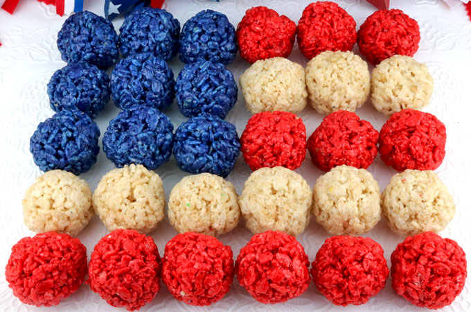 Red White and Blue Rice Krispie Bites - Yummy, bite-sized balls of crunchy, marshmallow-y delight. This is a 4th of July dessert that is easy to make and even yummier to eat. These colorful and festive 4th of July Treats are sure to please your loved ones. Pin this fun Patriotic snack for later and follow us for more fun 4th of July Food Ideas. #4thofJuly #fourthofjuly #4thofJulyTreats #RiceKrispieTreats #RedWhiteandBlue #TwoSistersCrafting