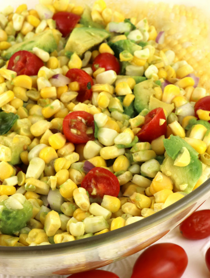 Corn and Avocado Summer Salad - corn, avocado & tomatoes combine for a light and delicious side dish for a hot summer day lunch or a summer night potluck or barbecue.  Summer Salads have never been easier, more delicious or more healthy.  Pin this yummy Summer Side Dish for later and follow us more more Summer Salad ideas.
