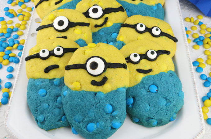 Minions M&M Cookies - these adorable and delicious yellow and blue Minion Cookies are chocked full of Mini M&M's and look just like the Minions from Despicable Me. What a great dessert for kids for a Minion Birthday Party or a Despicable Me Family Movie Night. Pin this yummy Minion Cookie Recipe for later and follow us for more Minion Food ideas.