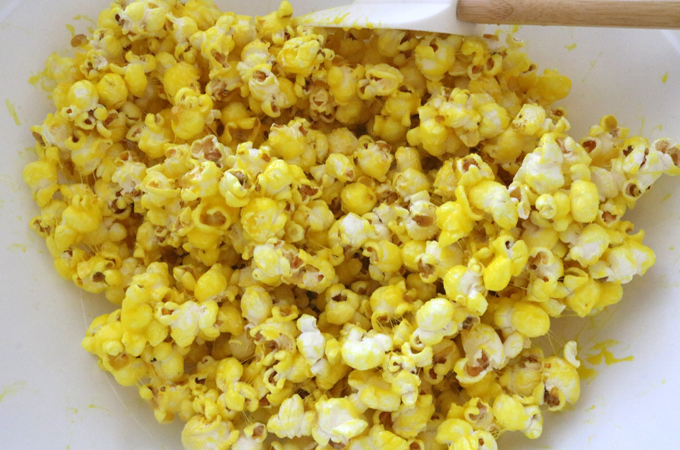 Stir the popcorn until it is completely covered with the yellow marshmallow mixture