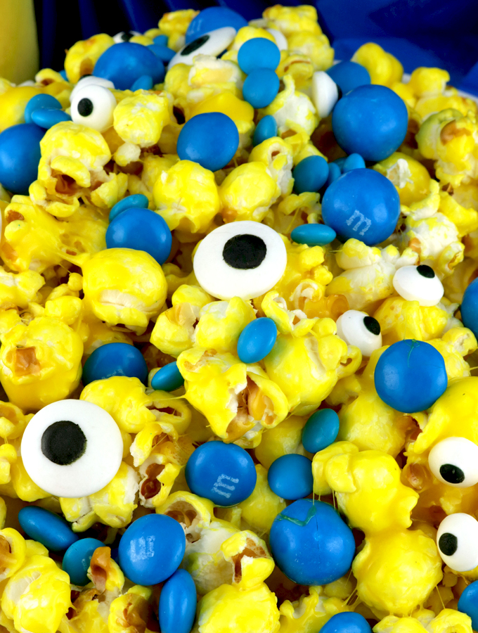 Minions Popcorn - sweet and salty popcorn mixed with M&M Candy and googly monster eyes will be a big hit with your family. It is both fun and delicious, a great combination! A fun anytime snack that would also be a great Party food at a Minions Birthday Party or a Despicable Me Family Movie Night. Pin this easy to make dessert for kids for later and follow us for more great Popcorn Recipe Ideas.
