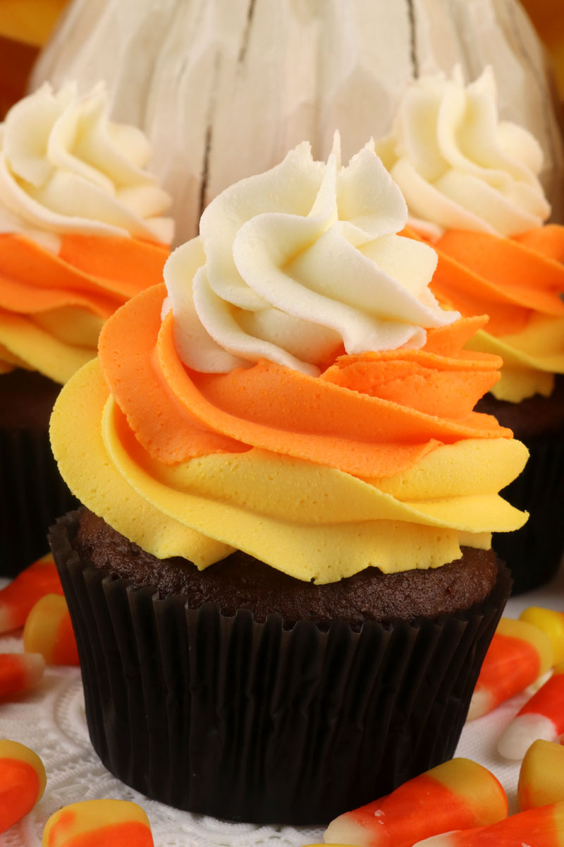 Candy Corn Swirl Cupcakes - these delicious Halloween Cupcakes looks like Candy Corn but tastes like chocolate cupcakes topped with delicious Buttercream Frosting. These yummy Halloween treats feature our Best Buttercream Frosting in Halloween colors and they are sure to become your go-to Halloween dessert. Pin this Halloween Cupcake for later and follow us for more great Halloween food ideas.