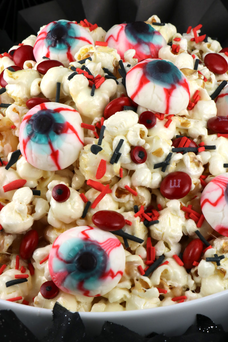 Creepy Eyes Halloween Popcorn - this fun treat is sweet, salty, delicious and chock full of creepy gummy eyeballs, chocolate candy and spooky sprinkles. This fun Halloween Dessert will both scare and delight your guests at this year's Halloween Party. Pin this easy to make Halloween Treat for later and follow us for more fun Halloween Food ideas.