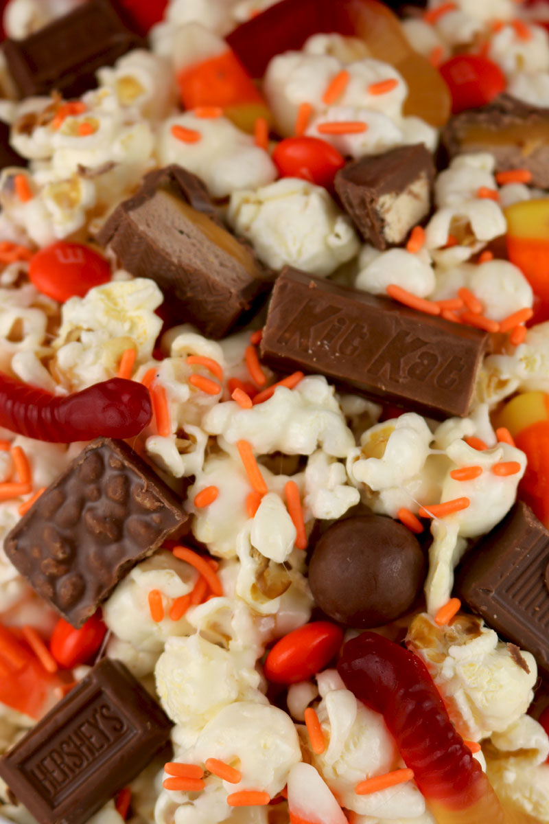 Left-Over Halloween Candy Popcorn - a yummy popcorn treat chock full of left-over Halloween Trick or Treat Candy.  Sweet, salty, crunchy and delicious, this Halloween dessert is so easy to make. Pin this great Halloween Treat for later and follow us for more fun Halloween Food ideas.