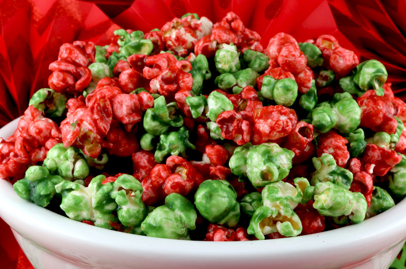 Christmas Caramel Corn - Yummy, buttery caramel corn in pretty Red and Green for the Holidays. And no corn syrup necessary in this easy homemade Christmas treat. This fun and delicious Christmas Popcorn would be a great Christmas dessert idea for a Christmas Party or a holiday gift basket. Pin this easy Holiday Dessert for later and follow us for more great Christmas Food ideas. #Popcorn #Christmas #CaramelCorn #ChristmasDesserts #ChristmasTreats