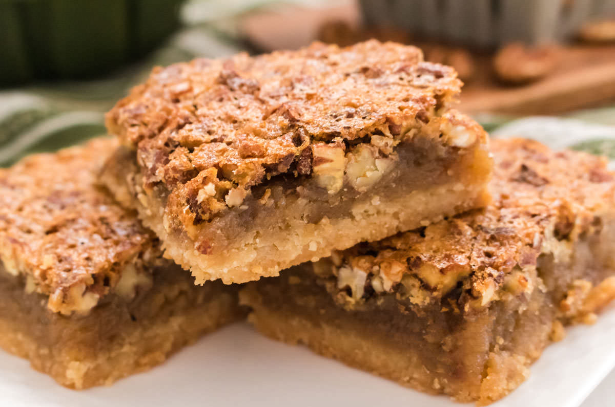 Closeup on a stack of three Pecan Pie  Bars sitting on a white plate.