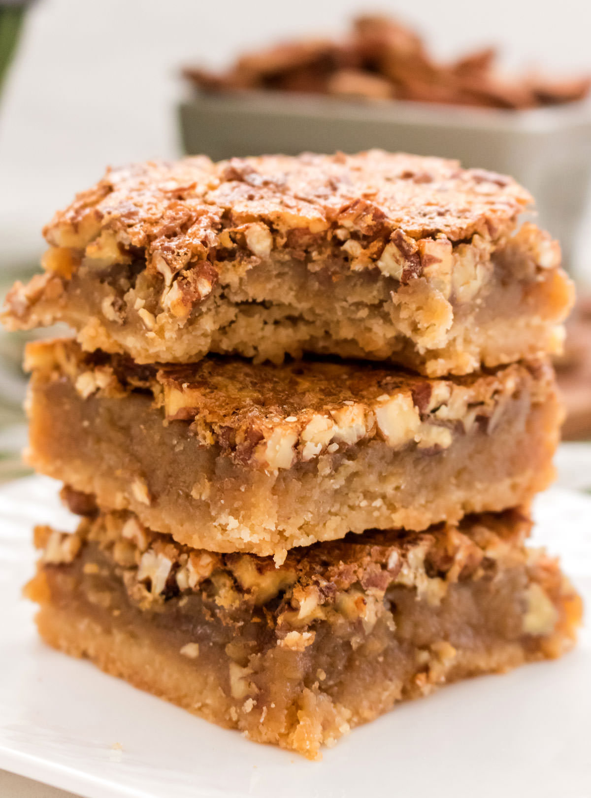 Closeup on a stack of three Pecan Pie Bars sitting on a white plate, the top one has a bite taken out of it.